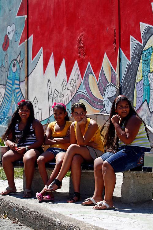 Central America, Cuba, Havana. Local girls on bench in Muraleando neighborhood.
