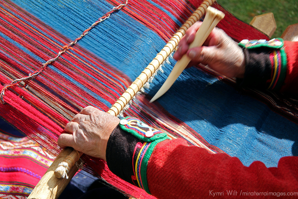 South America, Peru, Chinchero. Chinchero Cooperative weaver demonstrates using loom and tool.
