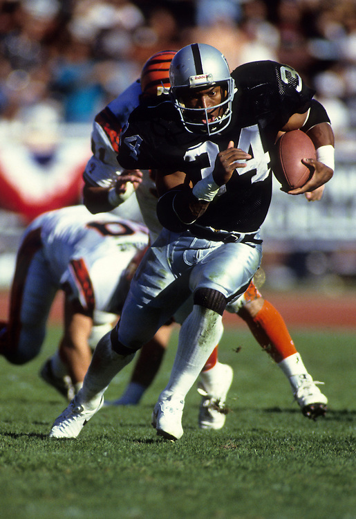 LOS ANGELES, CA-November 1990:  Running back Bo Jackson of the Oakland Raiders runs with the ball during a game versus the Kansas City Chiefs at the LA Coliseum, Los Angeles California.  Jackson played for the Oakland Raiders from 1987-1990.  (Photo by Ron Vesely)