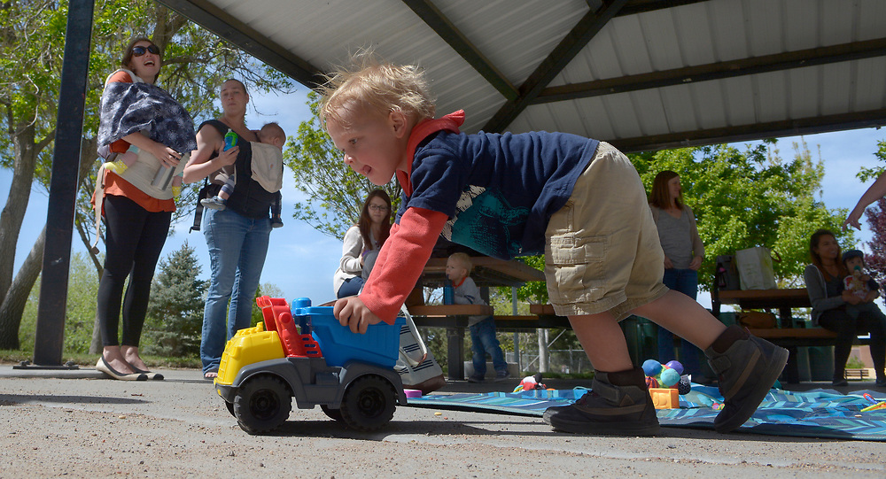 gbs042417a/ASEC -- Keaton Pierce, 2, plays with a toy truck while Marta Ossolinska of Albuquerque, left, and his mother, Karen Pierce of Albuquerque, second from left, visit during a new members meeting of the Desert Mommies Club at Academy Hills Park on Monday, April 24, 2017. The club has events every weekday where children and mothers can socialize. Desert Mommies Club is a local group of dynamic women who come together on a regular basis to share in the fun and exciting world of motherhood. Their common goal is to provide mother-to-mother support while enjoying the individual joys and challenges of motherhood. (Greg Sorber/Albuquerque Journal)