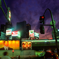 Image of harrassed salaryman (Japanese businessman) with neck in a brace on a billboard by railway tracks next to Shinjuku station, and Nishi-Shinjuku skyscrapers behind.