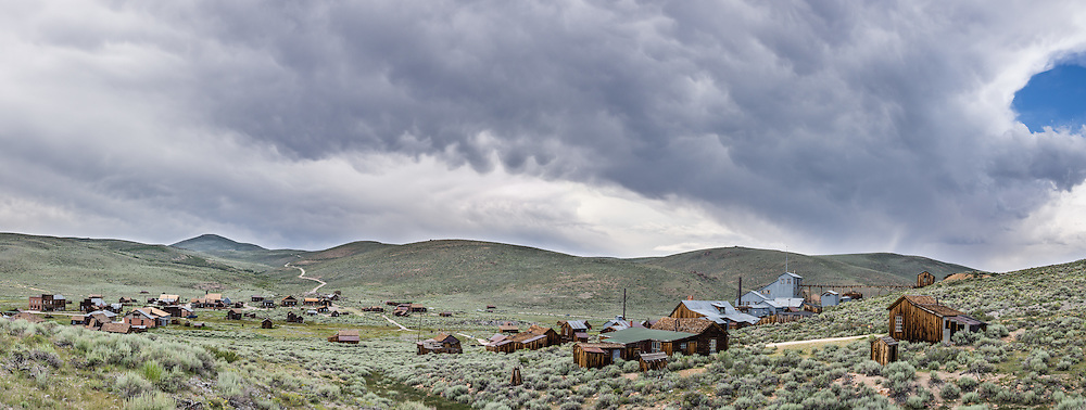 """Afternoon thunderstorm clouds loom over a panorama of historic Bodie and its Standard Stamp Mill. Bodie is California's official state gold rush ghost town. Bodie State Historic Park lies in the Bodie Hills east of the Sierra Nevada mountain range in Mono County, near Bridgeport, California, USA. After W. S. Bodey's original gold discovery in 1859, profitable gold ore discoveries in 1876 and 1878 transformed """"Bodie"""" from an isolated mining camp to a Wild West boomtown. By 1879, Bodie had a population of 5000-7000 people with 2000 buildings. At its peak, 65 saloons lined Main Street, which was a mile long. Bodie declined rapidly 1912-1917 and the last mine closed in 1942. Bodie became a National Historic Landmark in 1961 and Bodie State Historic Park in 1962. This panorama was stitched from 4 overlapping photos."""