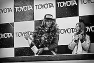 England's 1976 World Champion James Hunt, a cigarette dangling from his mouth and Penthouse Pet by his side, sprays the champagne after winning the 1977 United States Grand Prix at Watkins Glen. <br />