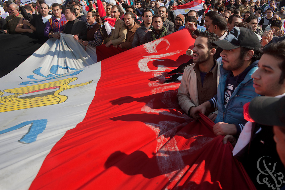 Egyptian protesters unfurl a large Egyptian flag during a pro-Mubarak march February 02, 2011in the Mohandiseen district of Cairo Egypt. Both pro and anti-Mubarak sides faced off today, battling for control of Tahrir square , which has been at the center of more than a week of ongoing protests across Egypt. .(Photo by Scott Nelson)