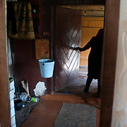 Amelie Volujevich, 76, who lives alone in the house where she grew up, walks outside to finish her daily chores on Sept. 16, 2009, in the village of Trashyane, near the border with Lithuania. The village used to have 70 homes with about 300 residents. Now less then 25 people live in the village with less than 10 staying year round.