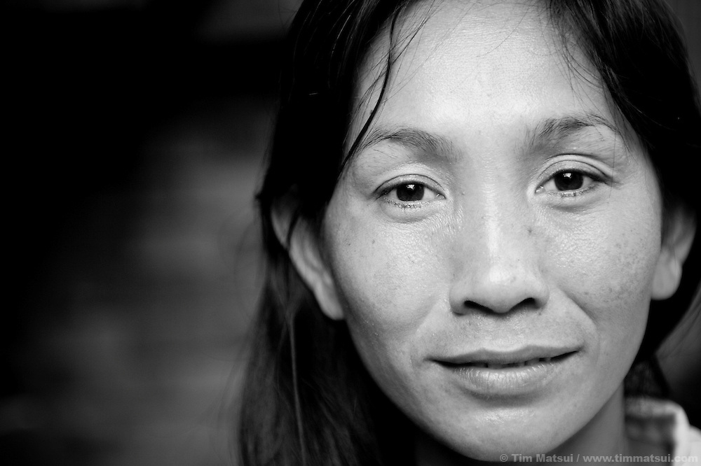 "Wue, a prostitute living in a slum where ""Acting for Women in Distressing Situations"" (AFESIP) conducts outreach and provides services, in Phnom Penh, Cambodia. Wue, 30, was previously a small business owner but turned to prostitution as a result of her economic situation. The slum's permanent structure, a decaying four story building known simply as 'The Building', was built in the 1960's as transitional housing and now hosts a shantytown where many of the city's poor live, including many prostitutes, and is believed to have the highest rate of HIV infection in the city. AFESIP hands out free condoms, instructs prostitutes on HIV prevention, and conducts outreach in case the prostitutes need medical services, choose to leave their profession, or can report on cases of sex trafficking. AFESIP offers housing, education, training, and counseling for women who are victims of sex trafficking, worked as prostitutes, or are escaping domestic violence. Founded by Somaly Mam, who herself was once a prostitute and victim of trafficking and domestic abuse, AFESIP has three facilities in Cambodia and works with other NGO's to provide long term care for the women."