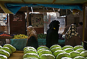 Palestinian women walk past a cart of cabbages at the Friday market in Rafah, Gaza January 16, 2009. Rafah residents have found ways to settle into a somewhat normal routine, venturing to market, to pray, and to visit friends despite the ongoing siege and bombing of the Gaza strip by Israeli forces. (Photo by Scott Nelson/World Picture Network for the New York Times)