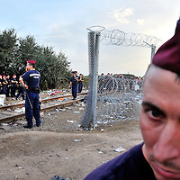 Hungarian police at 17:30 on 14th September controlling the gap in Hungary's recently strengthened razorwire border fence along an old railway line - blocking the route to refugees. Many thousands of whom have used this crossing point to enter Hungary in recent weeks. The numbers increased massively prior to the deadline of thenext day, 15th September announced by the Hungarian authorities to seal its fence, and close so-called illegal crossing points, as well as bringing in heavily restrictive terms for refugees wishing to enter Hungarian territory. This closeure of the gap several hours early was unexpected. Until midnight refugees continued to be allowed to enter the coutry via a nearby official border cossing, and then bused without registration direct to the local train statin at Röszke, where special tarins were laid on to take then directly to the Austrian border.