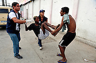 """Jacarézinho Favela, North Zone of Rio de Janeiro. Military police and social workers of the City looking for crack users in the early morning to take them to a selection center. Minors will be directed to detention rehab centers. An adult from the """"cracolândia"""" accustomed to the raids of social services pretends to assist officials to bring a recalcitrant young man. /// Favela Jacarézinho, Zona Norte de Rio. La police militaire et les assistants sociaux de la Mairie recherchent les usagers de crack au petit matin, pour les emmener dans un centre de tri. Les mineurs seront dirigés vers des centres fermés. Un adulte de la cracolândia """"habitué"""" à la rafle des services sociaux fait mine d'aider les fonctionnaires à emmener un jeune récalcitrant."""