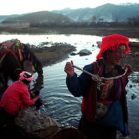 """ZHONGDIAN COUNTY, DECEMBER 19, 2000: Tibetan Kampa nomads wash their clothes and water their ponies at a spring at the end of the day, Yunnan province , December 19, 2000..Mt. Meili is the highest peak in Yunnan province and according to supporters from Deqin county, it's a """"proof"""" that the 'real"""" Shangri-La is located in deqin county. The fictuous Mt. Karakal which is described in James Hilton's Lost Horizon, alledgedly is modelled on Mt. Meili in Yunnan province.."""