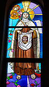 "A stained glass image of St. Therese of Lisieux holding a cloth with an image of Jesus, at the Carmelite monastery in Denmark, Wis. Next to her is a scroll with the words, ""In the heart of the church I will be love,"" from her autobiography, ""The Story of a Soul."" (Sam Lucero photo)"