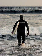 A man walks with his surfboard into the ocean for a surf session at Rockaway Beach, Queens, NY.