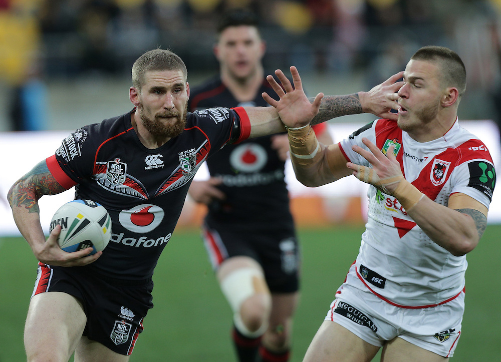 Sam Tomkins of the New Zealand Warriors fends off a challenge from Euan Aitken of the Dragons during their round 22 NRL match at Westpac  Stadium, Wellington on  Saturday, August 08, 2015. Credit: SNPA / David Rowland