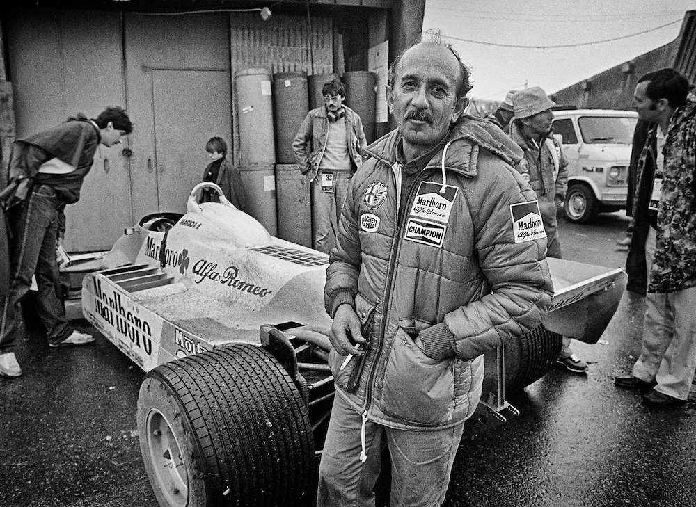 Ermanno Cuoghi, seen here in the aftermath of the 1981 Canadian Grand Prix was a legendary racing mechanic that had partnered with  Niki Lauda to win two World Driver's Championships (1975, 1977) at Ferrari. Following his public firing from Ferrari for agreeing to join Lauda at Brabham in 1978, he became part of the political intrigue that lead Lauda to walk away from Ferrari two races before the end of the 1977 season. <br /> <br /> He was a great racing friend and a source of infinite inside information. <br /> <br /> He also was a great practical joker. In one case during 1977, he insisted that I to go inside a motorhome to give Lauda photographs from the previous year. In fact, he nearly pushed me up the stairs. I entered to find Lauda, Carlos Reutemann and Mauro Forghieri in a deep de-brief; their stares were sterilizing. I nodded, dropped the photos and charged out. Cuoghi met at the bottom of the stairs.<br /> <br /> I blurted out,&quot;How could you do that? I wasn't supposed to be in there. I never felt so much cold.&quot;<br /> <br /> Cuoghi winked, &quot;Now you know what it's like to drive for Ferrari these days.&quot;