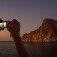 Tourist capturing a twilight photo of Sleeping Lion Rock off San Cristobal, Galapagos