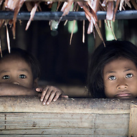 A girl and boy peer out from their hut in a Batak village in Palawan, the Philippines
