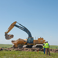 2 surveyors in front of excavator on wind project site