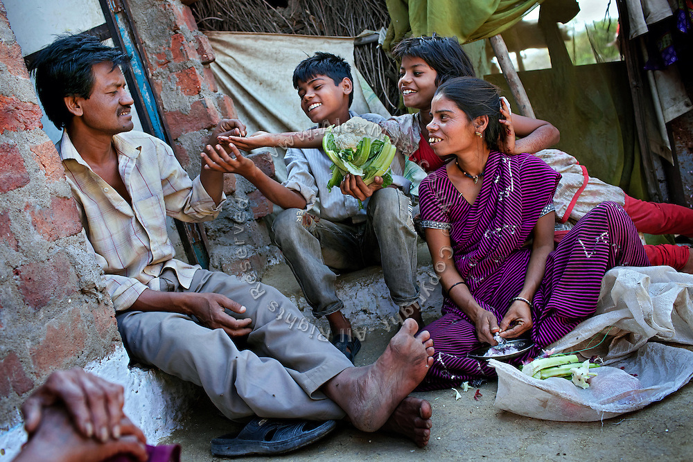 Poonam, 10, sitting next to her brother Ravi, 12, is receiving a coin from their father, Suresh Jatev, 43, in the front yard of their newly built home in Oriya Basti, one of the water-contaminated colonies in Bhopal, central India, near the abandoned Union Carbide (now DOW Chemical) industrial complex, site of the infamous '1984 Gas Disaster'. Sangita Jatev, 39, Poonam's mother, is sitting nearby and preparing vegetables for dinner.