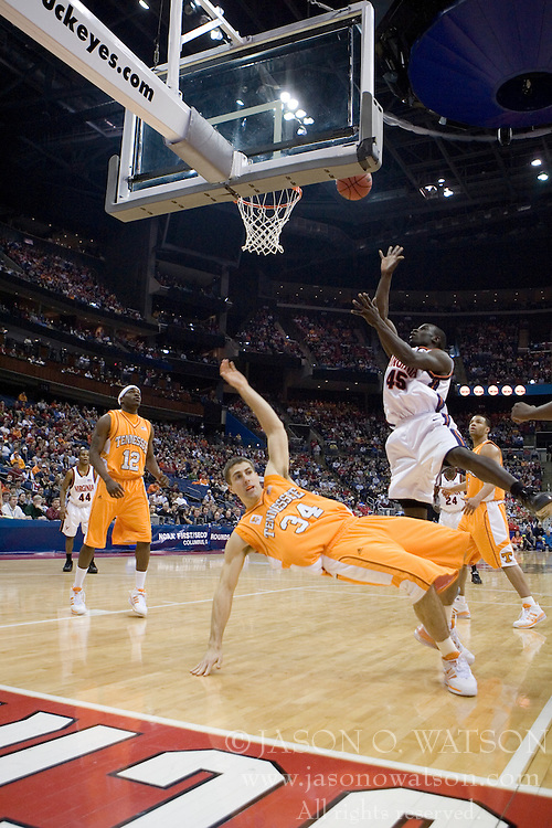 Tennessee Volunteers forward Ryan Childress (34) appeals for a charge but was not given the call as Virginia Cavaliers guard/forward Solomon Tat (45) scores on the play.  The #4 seed Virginia Cavaliers were defeated by the #5 seed Tennessee Volunteers 77-74 in the second round of the Men's NCAA Tournament in Columbus, OH on March 18, 2007.