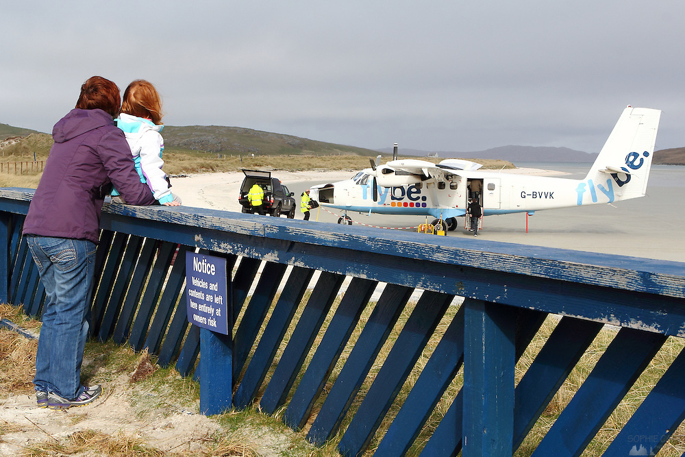Onlookers watch the Twin Otter being loaded at Barra Beach, Outer Hebrides, Scotland