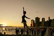 A ballet dancer strikes a pose  by the East River at sunset with the Manhattan skyline in the background