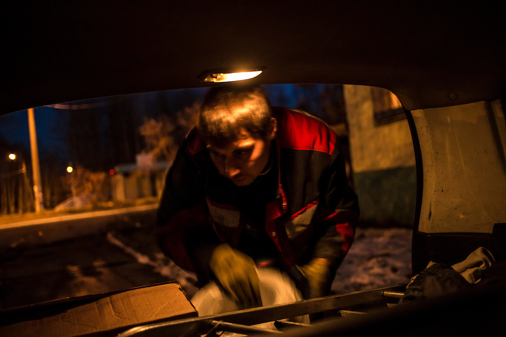 Maxim loads the trunk of his car after work on Saturday, October 19, 2013 in Baikalsk, Russia.