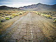 An original alignment of the Lincoln Highway looking eastward in the Nevada desert between Austin and Fallon. The stretch of pavement is visible and accessible from modern day US Route 50. Travelers can pull over and walk out to the pavement, which shows the narrower lane width of roads past. <br /> <br /> /// ADDITIONAL INFORMATION: 5/12/11 - 34travel.Lincoln.East.0929.sp - STUART PALLEY Lincoln Highway West