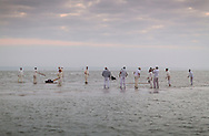 In the dawn light, members of the Royal Southern Yacht Club warm-up while waiting for the Island Sailing Club to  play their annual cricket match on the Bramble Bank in the centre of The Solent. The teams from Hamble, Hampshire and Cowes, Isle of Wight play their eccentric competition in the middle of the busy shipping lane in a tradition dating back to the 1950's. The teams take it in turns to win in alternate years. This year the ISC won and hosted breakfast following the game which commenced at 06:30am.<br /> Picture date: Thursday 11th September, 2014.<br /> Picture by Christopher Ison. Contact +447544 044177 chris@christopherison.com