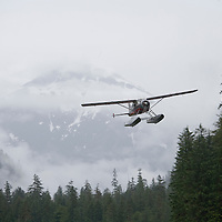 USA, Alaska, Misty Fjords National Monument, Float plane flying low over coastal rainforest along Rudyerd Bay on flightseeing tour on foggy morning