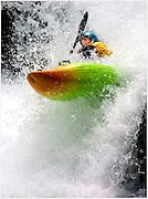 kayaker riding through white water rapids