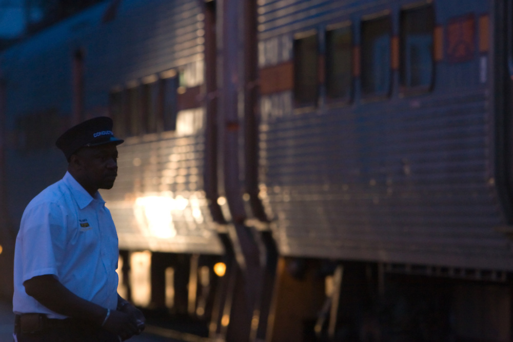 A South Shore railroad conductor helps passengers board the train as his train makes its stop in the street in Michigan City, IN.