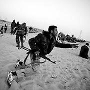 Des combattants rebelles se mettent à l'abri des balles tirées par l'armée loyaliste, le 25 mars 2011 à une dizaine de kilomètres de la ville d'Aj Dabiya.