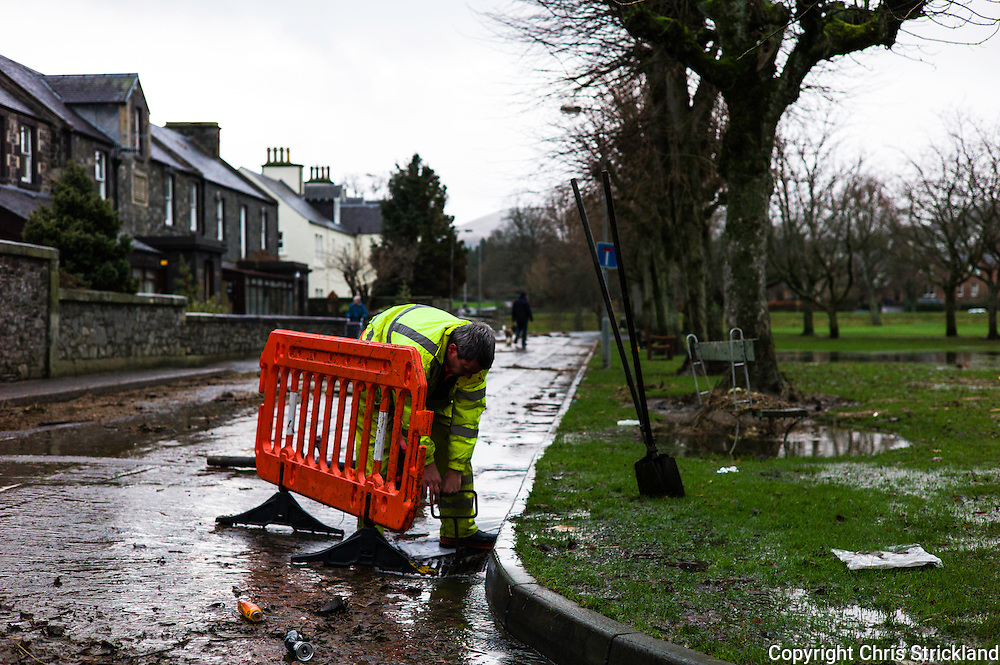 Peebles, Scotland, UK. 31st December 2015. The Borders town of Peebles cleans up this morning after the River Tweed flooded the town. Dog walkers share the streets with local council workers cleaning up after Storm Frank.