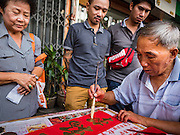 """18 JANUARY 2017 - BANGKOK, THAILAND: People watch a traditional Chinese calligrapher write out New Years greetings in Bangkok's Chinatown district, before the celebration of the Lunar New Year. Chinese New Year, also called Lunar New Year or Tet (in Vietnamese communities) starts Saturday, 28 January. The coming year will be the """"Year of the Rooster."""" Thailand has the largest overseas Chinese population in the world; about 14 percent of Thais are of Chinese ancestry and some Chinese holidays, especially Chinese New Year, are widely celebrated in Thailand.       PHOTO BY JACK KURTZ"""