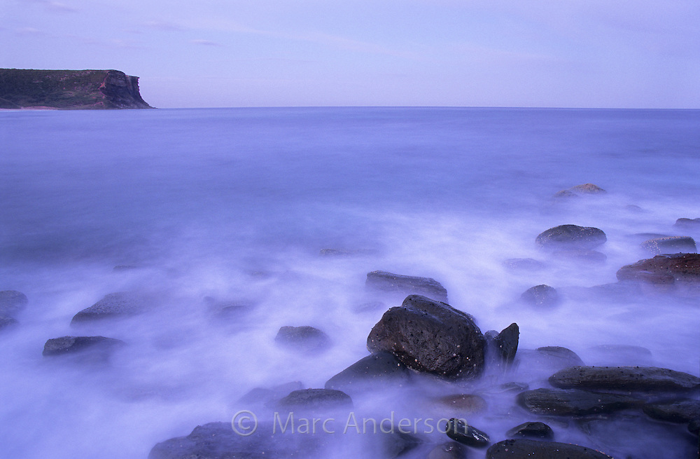 A rocky shore and misty sea at twilight, Little Garie Beach, Royal National Park, Australia.