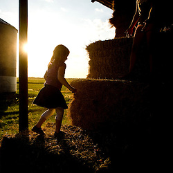 A young girl plays on bales of hay in a barn.