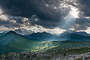 Crepuscular rays of sunlight break through clouds near Marmolada (Ladin: Marmoleda, German: Marmolata, 3343 meters / 10,968 feet elevation), the highest mountain in the Dolomites, or Dolomiti, a part of the Southern Limestone Alps, in northern Italy, Europe. The view looks westwards from a trail west of Gasthaus Passo di Giau. The Dolomites are honored as a natural World Heritage Site (2009) by UNESCO.