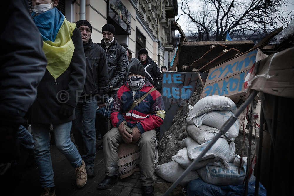 An anti-government protesters stand guard at one of the barricades defending Maidan Square against police and government supporters on December 15, 2013 in Kiev, Ukraine. Thousands of people have been protesting against the government since a decision by Ukrainian president Viktor Yanukovych to suspend a trade and partnership agreement with the European Union in favor of incentives from Russia was made recently.