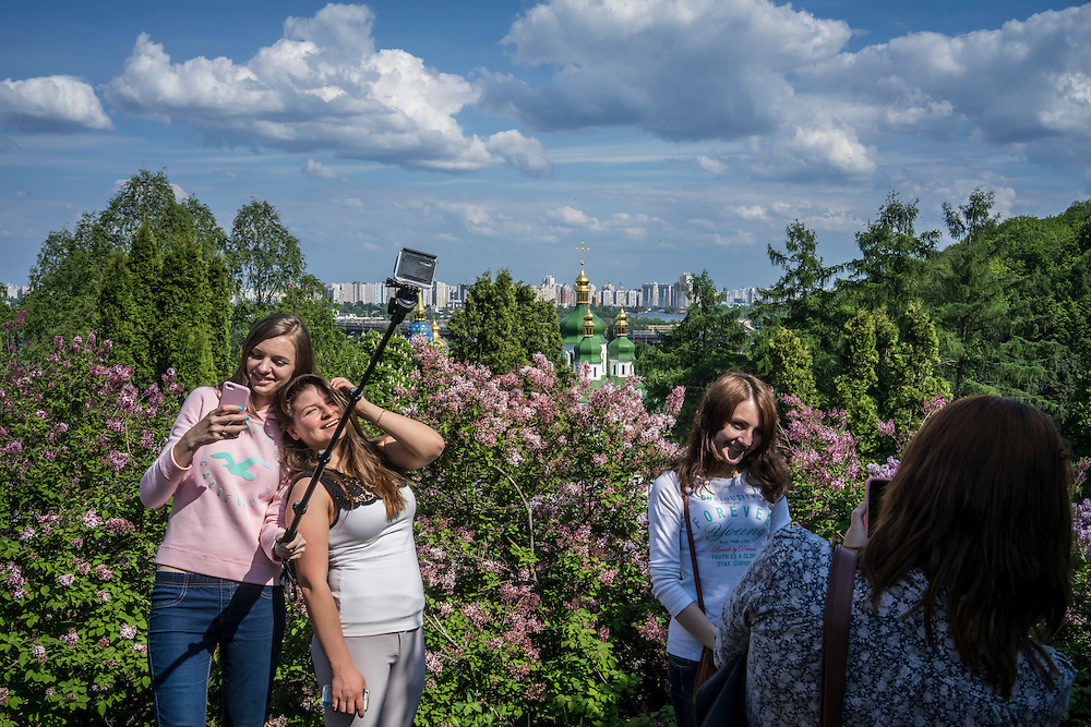 Women pose for pictures at the botanical gardens on Sunday, May 10, 2015 in Kyiv, Ukraine.