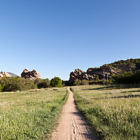 A hiking and biking path runs between protruding red rock strata in the South Valley Park Ken-Caryl Ranch Open Space in Colorado.