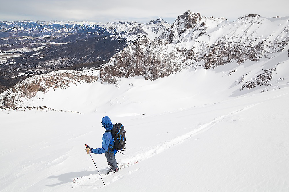 Backcountry skier Sterling Roop descends from the summit of Hayden Peak, San Juan Mountains, Colorado, with the Sneffels Range in the background.