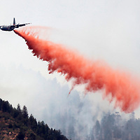 "A massive C-130 military cargo plane drops thousands of gallons of retardant on the Waldo Canyon fire west of Colorado Springs, Colorado June 26, 2012.  A fast-growing wildfire in Colorado forced 11,000 people from their homes at least briefly and threatened popular summer camping grounds beneath Pikes Peak, whose vistas helped inspire the patriotic tune ""America the Beautiful.""    REUTERS/Rick Wilking (UNITED STATES)"