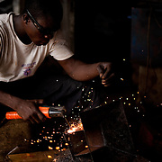 A welder makes charcoal braziers for cooking in a workshop in Agbogbloshie, a slum in Ghana's capital, Accra. The more inexpensive models are sold to market women for GHC3 to 4. The workshop may make as many as 100 per day.