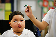 Noah Stout, 7, looks at a Matchbox car as he joins classmates in Hilary Leday's second grade class for the first time since being diagnosed with Diffuse Intrinsic Pontine Glioma (DIPG), a rare and non-operable tumor located on the brain stem, at Sinnott Elementary School in Milpitas, California, on August 29, 2013. (Stan Olszewski/SOSKIphoto)
