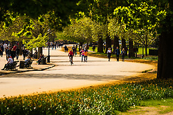 London, April 25th 2015. Despite the threat of forecasted showers, spring sunshine and warmth greets Londoners as they enjoy the Royal Parks in the capital. PICTURED: Cyclists, inline skaters and people out for a stroll enjoy the sunshine by The Serpentine in Hyde Park.