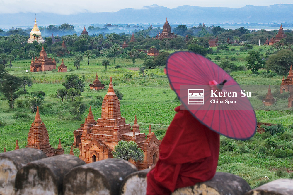 Monk in red with red umbrella with temples in Bagan, Myanmar