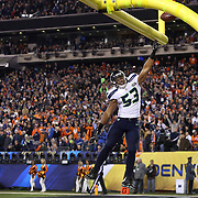 Superbowl MVP Malcolm Smith dunks the ball over the uprights as he scores a touchdown on a interception in the second quarter at Super Bowl XLVIII Sunday, Feb. 2, 2014, at MetLife Stadium in New Jersey. The pick-six gave the Seahawks a solid lead over the Broncos. (Joshua Trujillo, seattlepi.com)