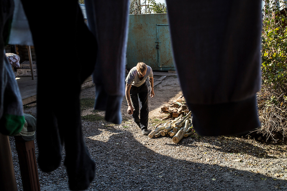A man, part of a group of internally displaced people who fled the besieged city of Donetsk and are now living in a small seaside resort that has become their home, unloads fire wood for winter heating on Tuesday, October 14, 2014 in Berdyansk, Ukraine. Photo by Brendan Hoffman, Freelance