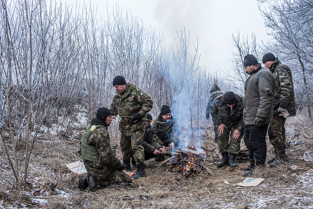 Ukrainian soldiers cook sausage over a fire along the road leading to the embattled town of Debaltseve on February 15, 2015 outside Artemivsk, Ukraine. A ceasefire scheduled to go into effect at midnight was reportedly observed along most of the front, save for near the embattled town of Debaltseve.