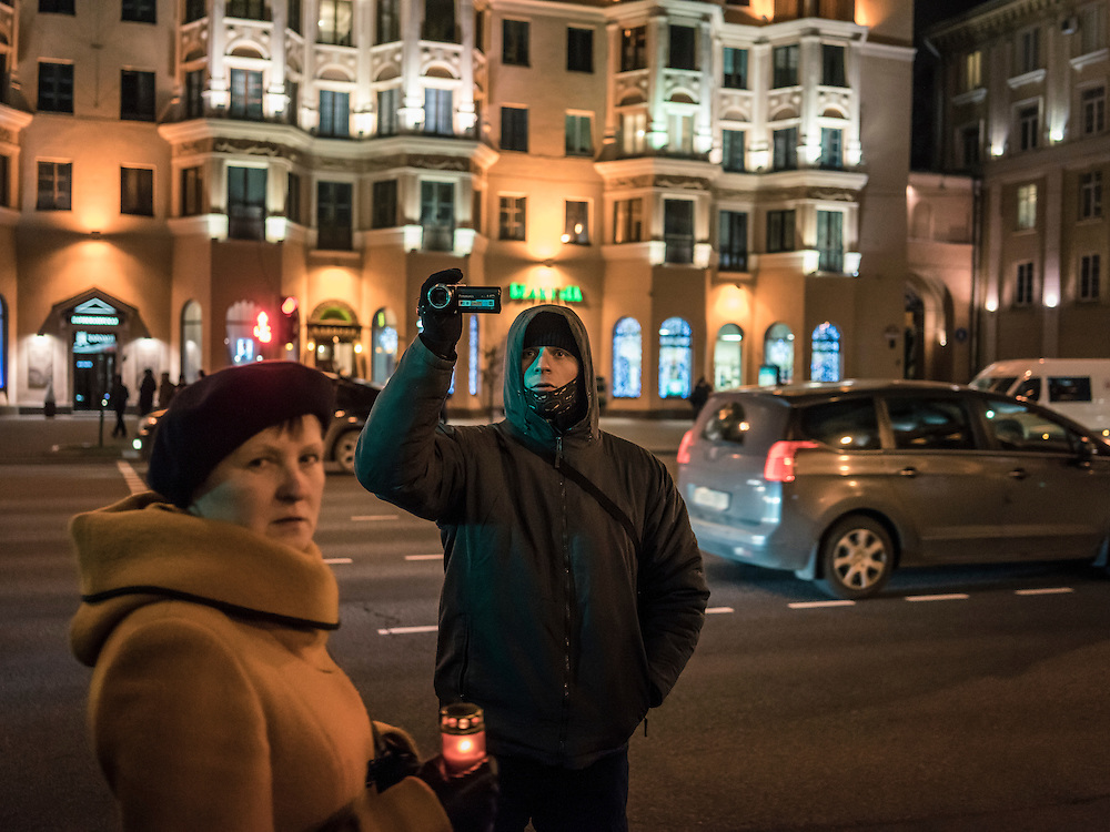 A man believed to be an undercover police officer videotapes a rally organized by Mikalai Statkevich, a former opposition presidential candidate and political dissident, to commemorate the nineteenth anniversary of a referendum which enshrined authoritarian changes in Belarus's constitution on Tuesday, November 24, 2015 in Minsk, Belarus.